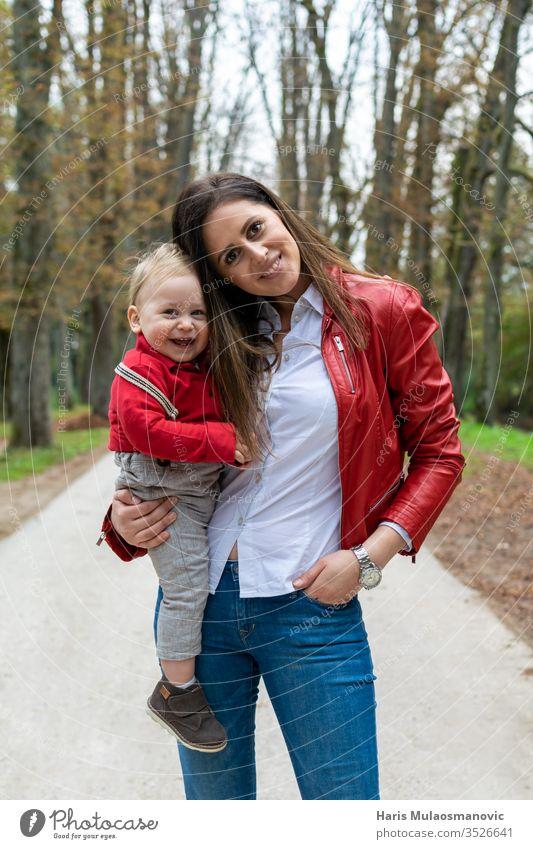 Glückliche Familie, junge Mutter, die ein 1-jähriges Kind hält und lächelt 1 Jahr alt 1 Jahr altes Baby Erwachsener Herbst schön Kaukasier Kombination niedlich