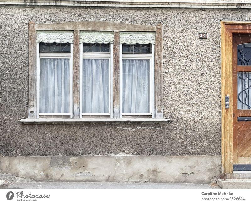 Drei Fenster neben einem Hauseinagang fenster tür Architektur alt verschnörkelt verzierungen Bauwerk Gebäude Menschenleer Farbfoto Außenaufnahme Fassade Mauer