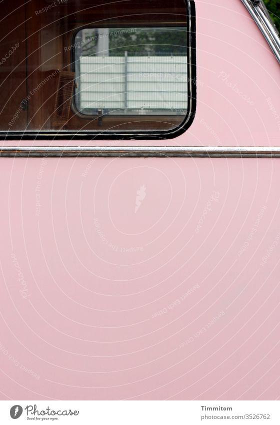 Fenster eines alten Wohnwagens - Teilansicht Vintage rosa Kunststoff Menschenleer retro Camping Durchblick Zaun