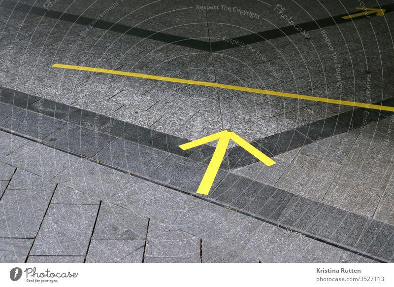 gelbe pfeile auf dem boden als abstands- und richtungsmarkierung markierungen klebeband distanz distanzmarkierung abstandshalter abstandsmarkierung einteilen