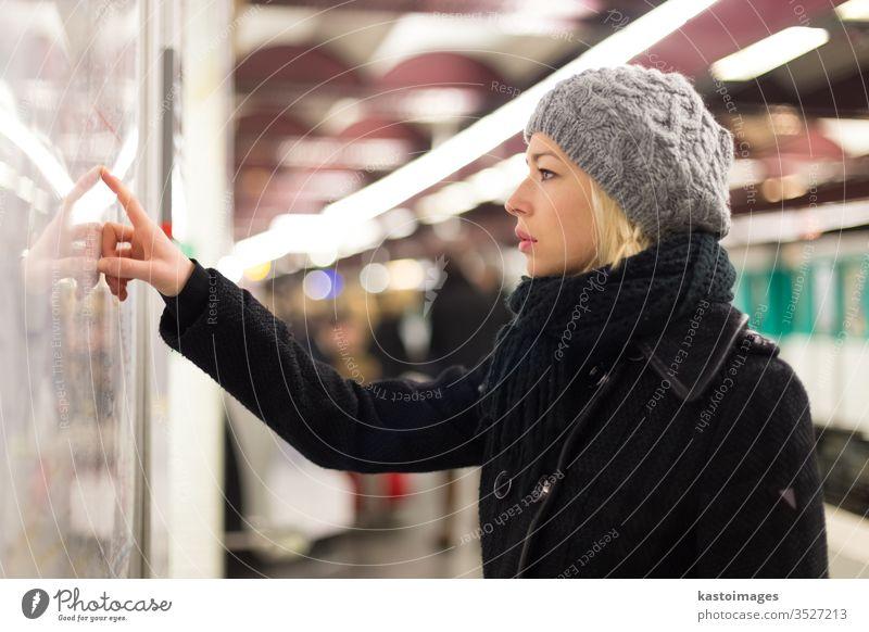 Dame schaut auf Kartentafel des öffentlichen Verkehrs. Landkarte U-Bahn Frau Station Arbeitsweg urban Panel Transport Zug Linie Großstadt Regie Öffentlich Suche