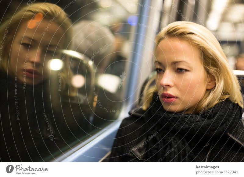 Frau schaut aus dem Fenster der U-Bahn. Verkehr Porträt Tube transpotation reisen urban Ansicht beobachten nachdenklich Ausflug Sitzen Einsamkeit Innenbereich