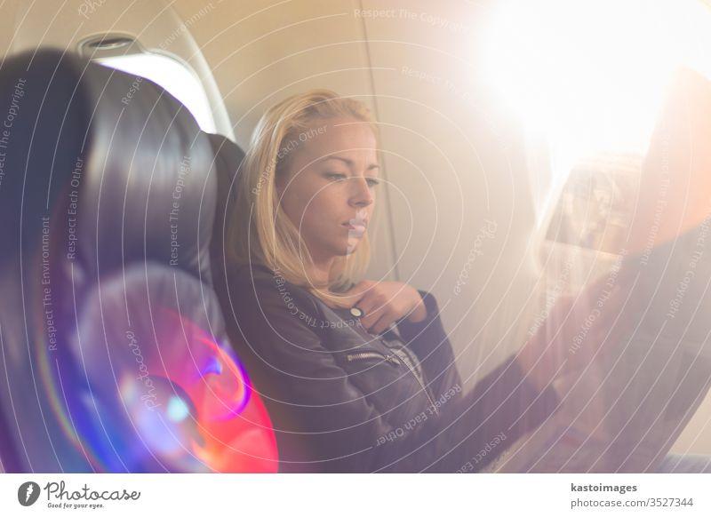 Frau liest Zeitung im Flugzeug. Passagier reisen Verkehr Ausflug lesen Sitz Ebene jung Air Transport Mädchen im Inneren Reise Kaukasier Kabine Fenster Fluggerät