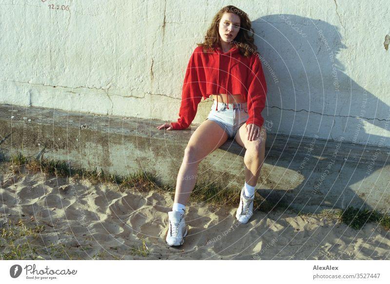 analoges Portrait einer jungen Frau mit roten Hoodie und Hotpants Mädchen schön groß sportlich schlank fit brünett Hot Pants Locken langes Haar Sneaker Beine
