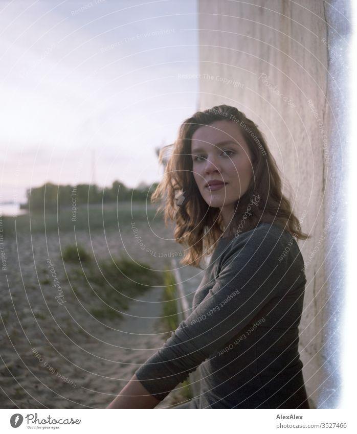 analoges Portrait mit Lichterscheinung einer jungen Frau im Kleid vor einer Wand Mädchen schön groß sportlich schlank fit brünett Locken langes Haar Beton Sand