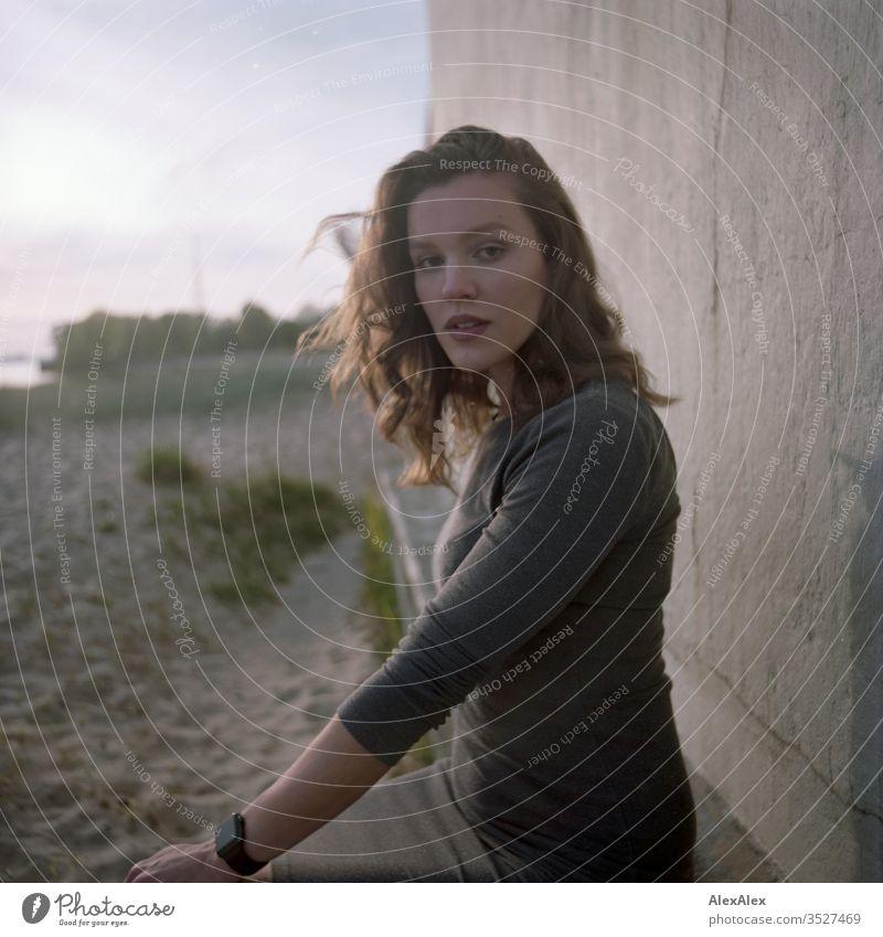 analoges Portrait einer jungen Frau im Kleid vor einer Wand Mädchen schön groß sportlich schlank fit brünett Locken langes Haar Beton Sand Strand Abend Körnung