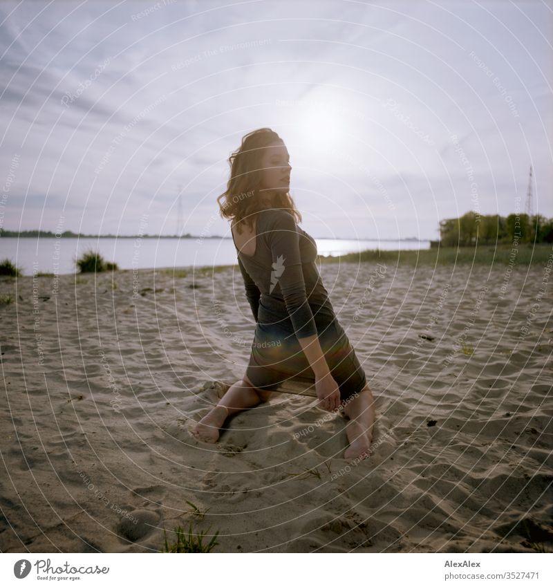 analoges rückwärtiges Portrait einer jungen Frau im Kleid am Strand beim Sonnenuntergang Mädchen schön groß sportlich schlank fit brünett Locken langes Haar