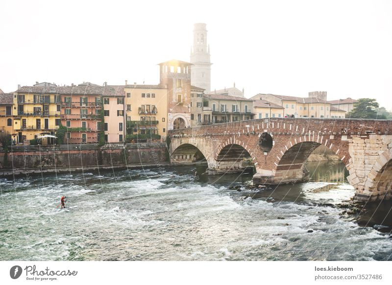 Flusssurfer bei Sonnenuntergang mit Blick auf die Stadt bei Ponte Pietra in Verona, Italien Surfer Sport Italienisch Turm Gebäude ponte pietra Brücke Europa