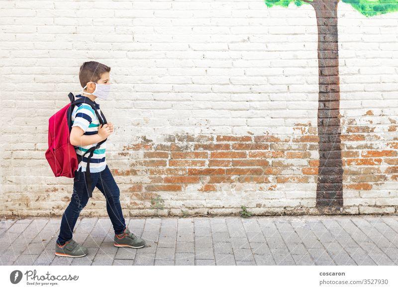 Kleiner Junge geht mit Schutzmaske zur Schule zurück zur Schule Rucksack Pflege Kind Kindheit Großstadt Klasse zugeklappt Hochschule Korona Corona-Virus