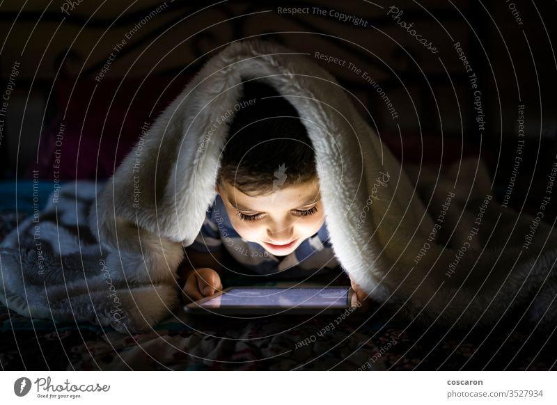 Kleines Kind benutzt eine mit einer Decke bedeckte Tablette allein Anwendung Bett Schlafzimmer Schlafenszeit Junge Kindheit Nur für Kinder spielende Kinder