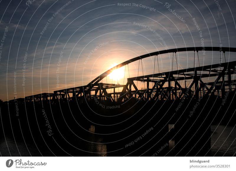 Wenn die Sonne hinter zwei Brücken über dem Main langsam untergeht. Metallkonstruktion Autobrücke Bahnbrücke Gegenlicht Kontrast Fluß Wasserweg Autoverkehr