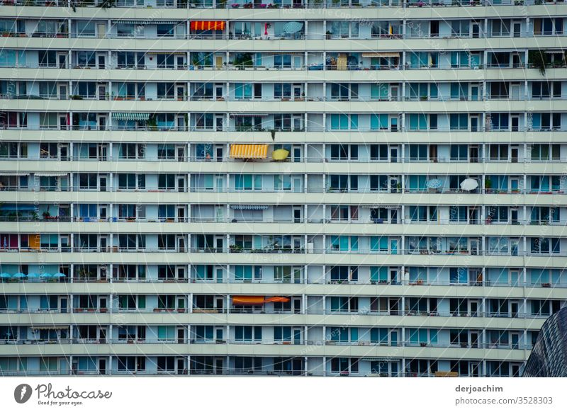 """"""" Mitten in Berlin  """" Plattenbau Fassade mit vielen Fenstern und Balkonen. Es gibt auch ein paar Sonnenschirme Hochhaus Architektur Gebäude Haus Außenaufnahme"""
