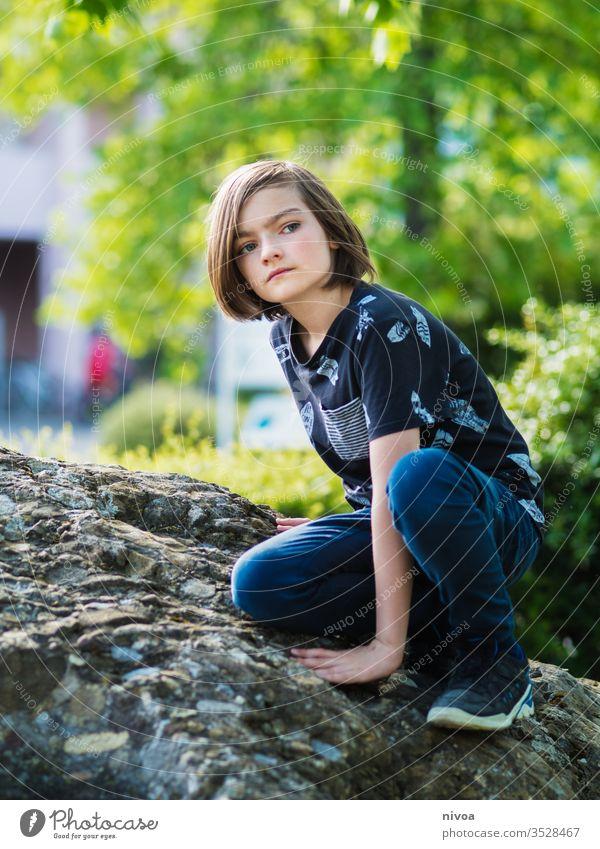 Junge sitzt auf einem Felsen Klettern aussruhen Sommer T-Shirt Kind blond Freude Farbfoto Natur Gras Tag grün Außenaufnahme jung Park Garten sonnig Kindheit