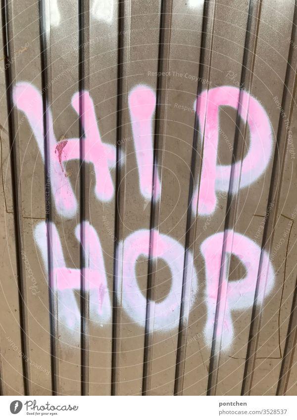 """Graffiti auf Garagentor aus wellblech. Text """"hip Hop"""" garagentor Hip Hop wort text illegal jugendkultur Menschenleer Buchstaben Außenaufnahme Farbfoto"""