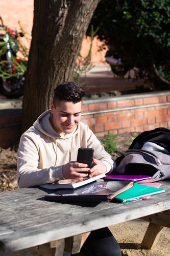 Junge Studentin, die in einem Park sitzt, während sie ein Mobiltelefon auf einem Holztisch benutzt eine Person Schüler Telefon Tisch Sitzen Mitteilung