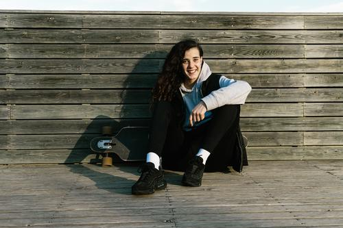 Teenager-Mädchen auf einem Longboard sitzend, an eine bewaldete Wand gelehnt Frau Lifestyle Person jung Sitzen Holzplatte Sommer Skateboard Großstadt urban