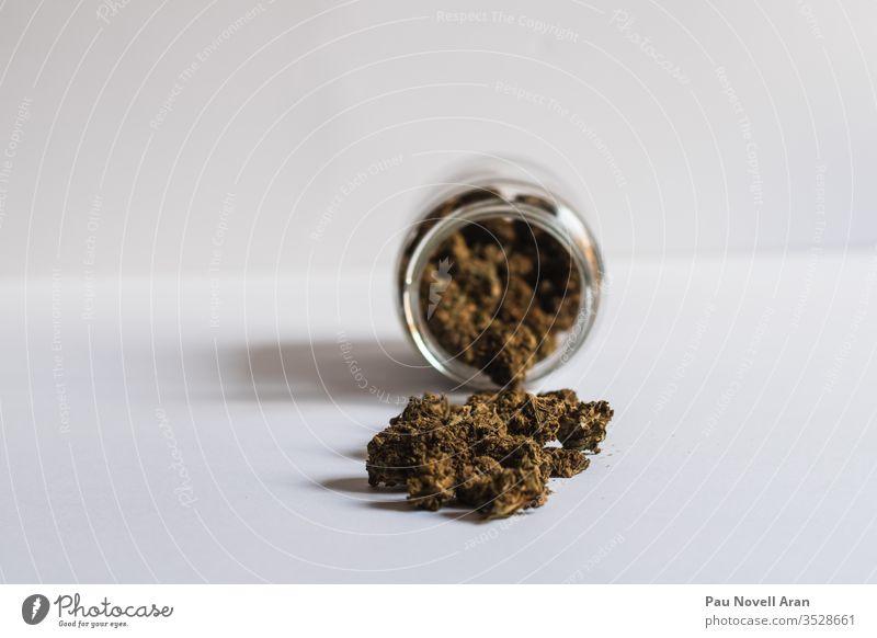 Ein Glas mit weißem Cannabis auf weißem Hintergrund Kraut Medizin Marihuana Sucht Dope ungesetzlich Marihuana / CBD cbd Textfreiraum Medikament ganja grün