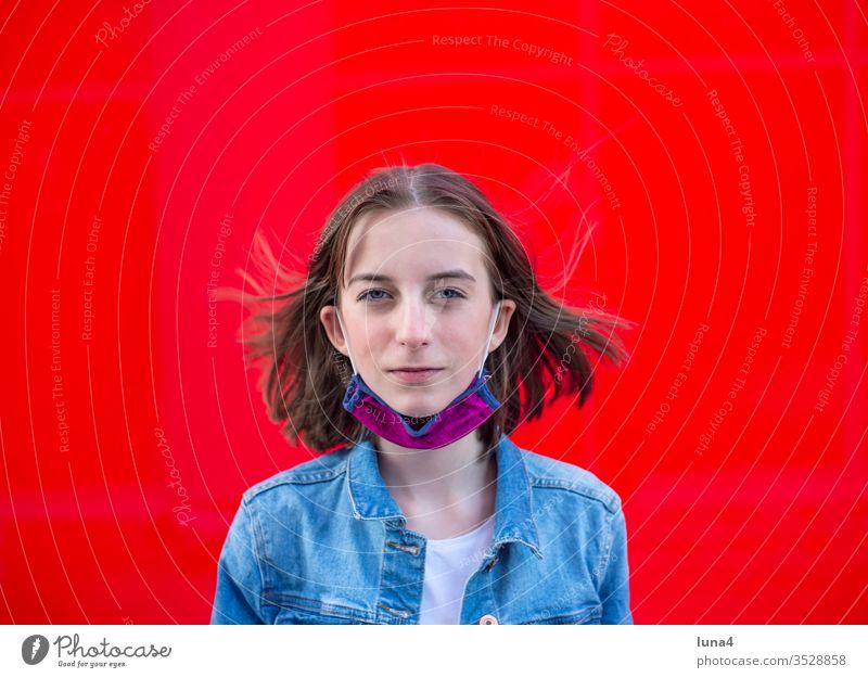Mädchen mit Mundschutz vor rotem Hintergrund Maske Atemschutzmaske Schutzmaske Mund-Nasen-Schutz Alltagsmaske selbstgenäht Jugendliche Virus Coronavirus besorgt