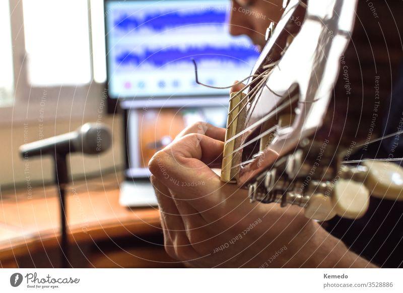 Person, die Gitarre spielt und den Ton mit Mikrofon und Technik zu Hause aufnimmt. Amateurmusiker, der Musik aufnimmt. spielen Hand Mann abschließen Unschärfe