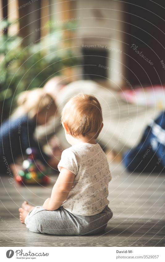 ein kleiner Junge beobachtet genau seine Umgebung um ja nichts zu verpassen Kind Kleinkind spielen beobachten Schwester kleines Kind niedlich aufmerksam