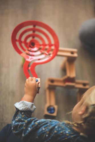 Mädchen Kind spielt mit Murmeln Holzspielzeug Kindheit niedlich Kleinkind Spielen Spielzeug Vogelperspektive Spaß haben Kindergarten Freude Kinderbetreuung