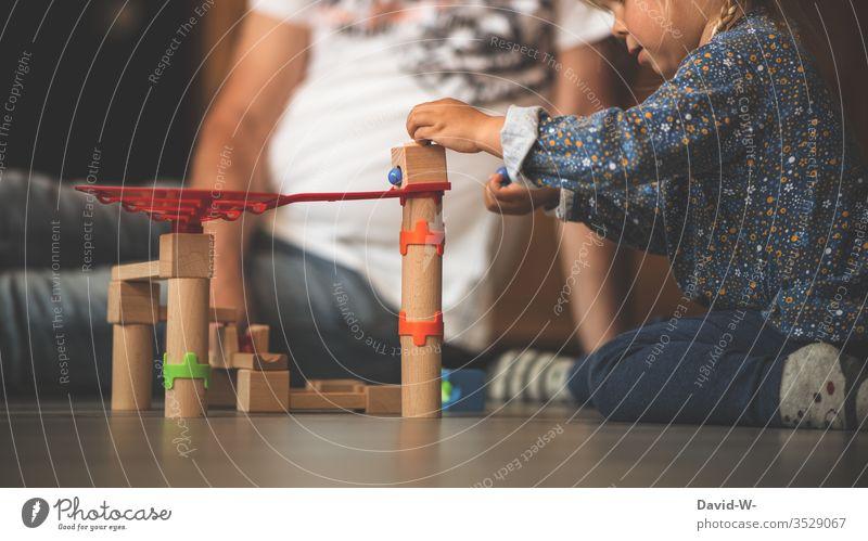 Kind spielt mit Holzspielzeug Spielzeug spielen Kinderzimmer Vater sitzen hocken drinnen Murmeln bauen kreativ spaß freude fröhlich konzentriert vorsichtig