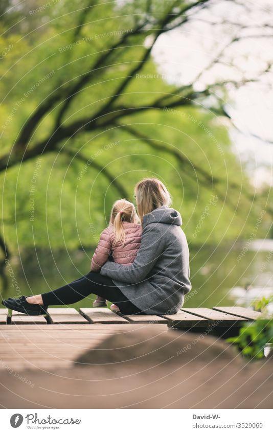 Mutter sitzt mit Kind auf einem Steg am Ufer eines Sees Mädchen Natur natürlich Familie Eltern Kindheit niedlich Liebe geborgenheit Ruhe verantwortung zusammen