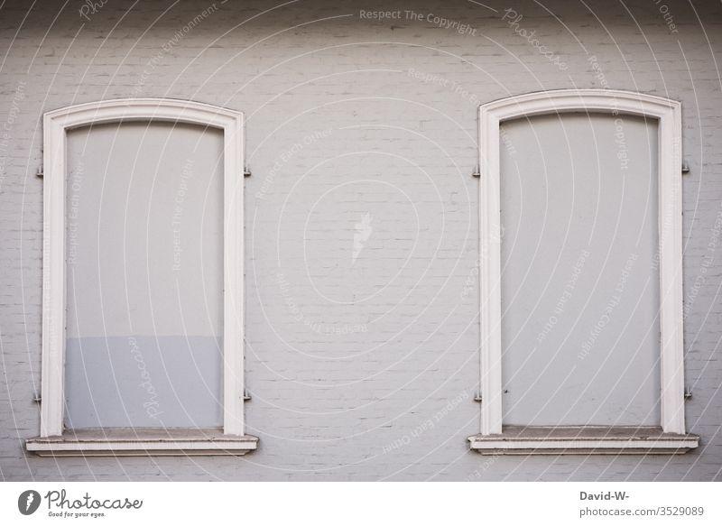 Hauswand - Fenster zugemauert zugemauerte Fenster geschlossen verriegelt Textfreiraum oben Textfreiraum links Textfreiraum rechts Gebäude Architektur grau hell