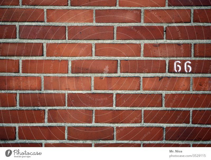 66 Hausnummer Ziffern & Zahlen Zeichen Mauer Wand sechsundsechzig Backsteinwand Backsteinmauer rot markierung linien oldstyle orientierung information