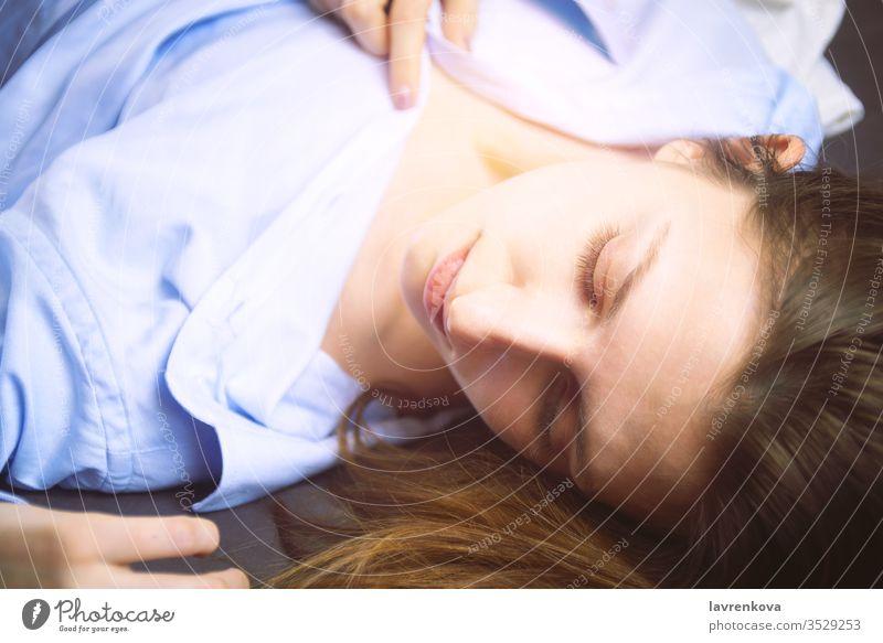 Nahaufnahme einer jungen schönen Frau in Blau, die im Bett liegt. Natürliche Schönheit. Selektiver Fokus. Filmstil romantisch Entspannungsbad Erholung Gesicht