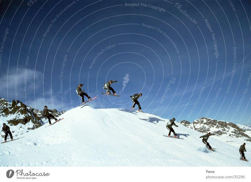Indi Grab (Sequenz) Berge u. Gebirge Schnee Sport springen Schönes Wetter Hügel fahren Abheben Reihe Doppelbelichtung Landen Blauer Himmel Snowboard Freestyle