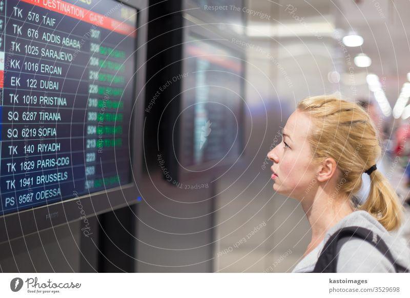 Passagier schaut auf die Fluginformationstafel. Flughafen Zeitplanung Information Anzeige reisen Frau jung Ausflugsziel Abheben Tourist Gepäck Reisender Mädchen