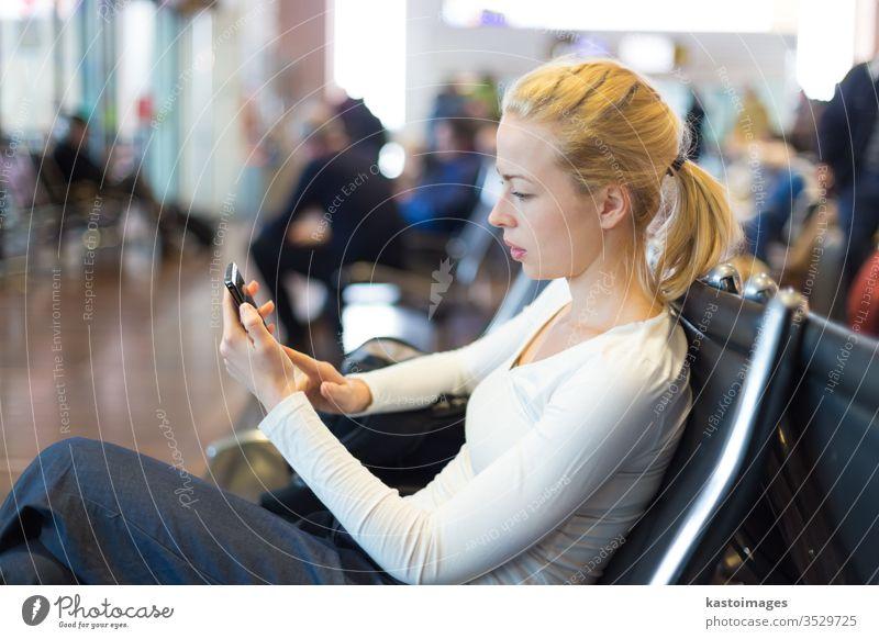 Weibliche Reisende, die während der Wartezeit ein Mobiltelefon benutzt. reisen Frau Reisender Station Passagier Telefon Gepäck Verkehr Flughafen Ausflugsziel