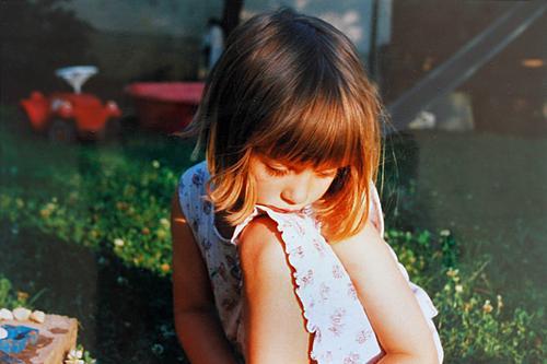 Nachdenkliches Mädchen im Kleid, sitzt auf der Wiese im Garten mit Spielzeug im Hintergrund und träumt, von Sonnenlicht bestrahlt Kind Kindheit Bobbycar Sommer