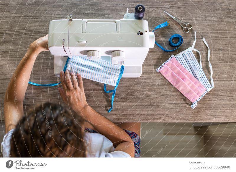 Frau, die zu Hause mit einer Nähmaschine Gesichtsmasken herstellt 2019-ncov oben Nahaufnahme Stoff Kleidung Bekleidung Gefecht Korona Corona-Virus Coronavirus