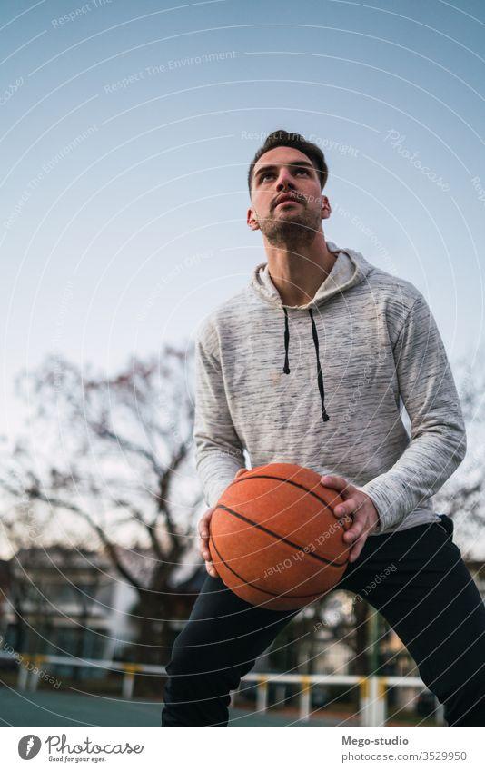 Junger Mann spielt Basketball. Training Ball männlich jung Sport Spiel Korb Spieler im Freien Straße Hand sportlich aktiv Spielplatz Club Freizeit spielen