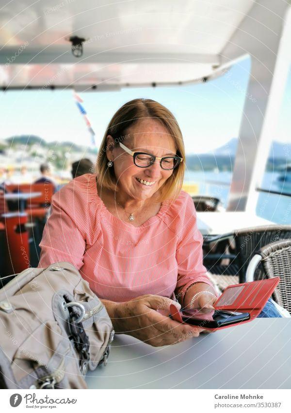 Ü70 Frau überprüft freudige Nachrichten auf dem Smartphone während einer Schifffahrt Seniorin pensioniert pensionärin bootsfahrt lachen Modus modisch verrotten
