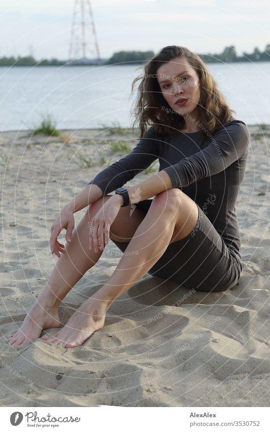 Porträt einer jungen Frau am Strand der Elbe Mädchen bereits schlank passen brünett Locken lange Haare Abend Einstellung Schönheit und Schönheit 18-25 Jahre