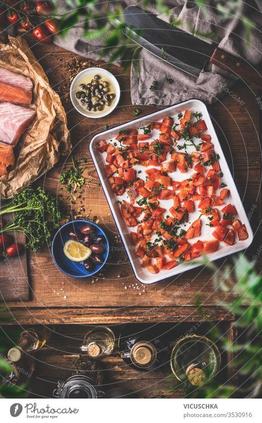 Kochen in einer Vintage-Küche.  Tomaten auf einem Backblech, roher Fisch, Kräuter und Gewürze, Olivenöl, Hackbeil auf einem rustikalen Holztischhintergrund. Ansicht von oben. Konzept der mediterranen Küche