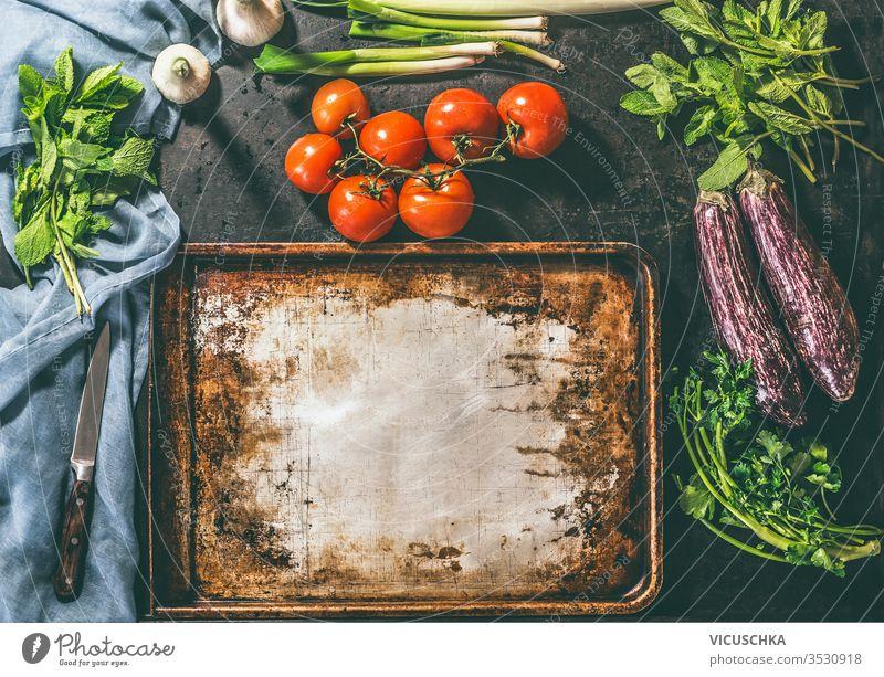 Kochen eines vegetarischen Gerichts mit Tomaten, Auberginen, Petersilie, Minzzwiebeln und Knoblauch Essen zubereiten Vegetarier Speise rustikal Hintergrund