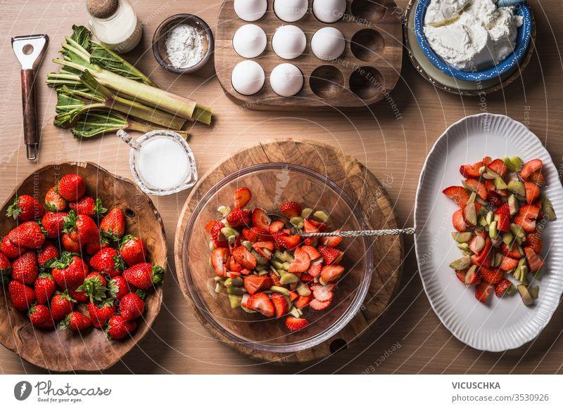 Frische Erdbeeren und Rhabarber auf hölzernem Tischhintergrund mit Zutaten für schmackhaftes saisonales Kochen oder Backen. Ansicht von oben. Gesundes und sauberes Essen. Paläo-Diät. Hausmannskost. Gartenfrüchte essen