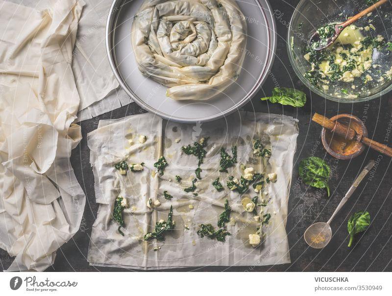 Backen der Zubereitung einer herzhaften Pastete mit Phyllo-Teigblättern, die mit Spinat und Feta-Käse gefüllt sind. Ansicht von oben. Balkan- oder orientalische Küche. Hausmannskost. Börek