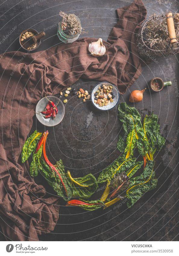 Lebensmittelhintergrund mit frischen, bunten Mangoldblättern auf dunklem, rustikalem Tischhintergrund. Hausgemachte Küche. Hintergrund farbenfroh Blätter dunkel