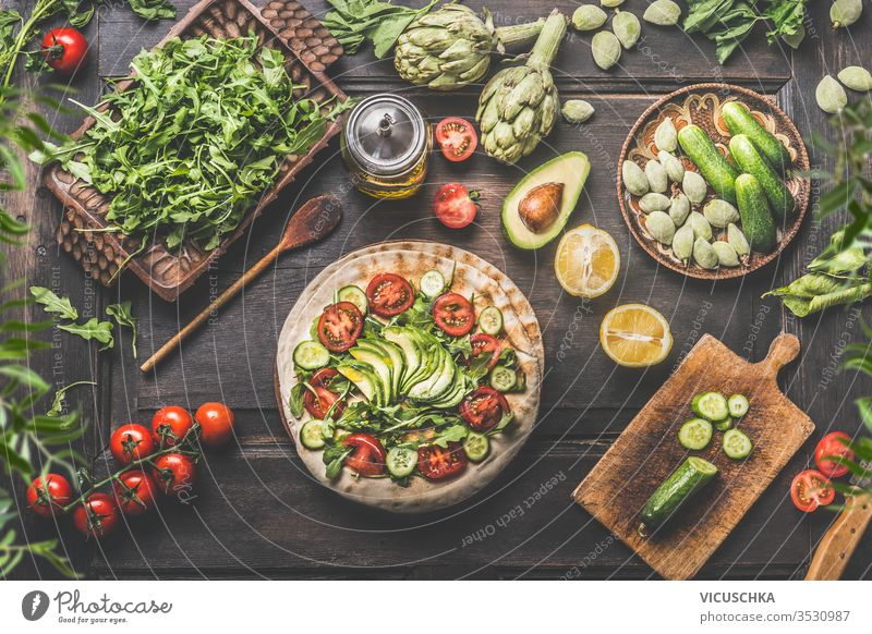 Gesunde vegetarische Zutaten für das Mittagessen. Tortilla umhüllt mit frischem Gemüse, Avocado, Olivenöl und Zitrone auf rustikalem Holzküchentisch, von oben gesehen. Vorbereitung zum Kochen. Veganes Essen.