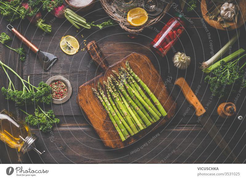 Frischer Bio-Spargel auf Holzschneidebrett. Geschnittene Kräuter, Olivenöl, Zitrone und Gewürze. Eingemachte Peperoni im Glasglas auf dunklem, rustikalem Hintergrund, Draufsicht. Gesunder Lebensstil. Hausmannskost