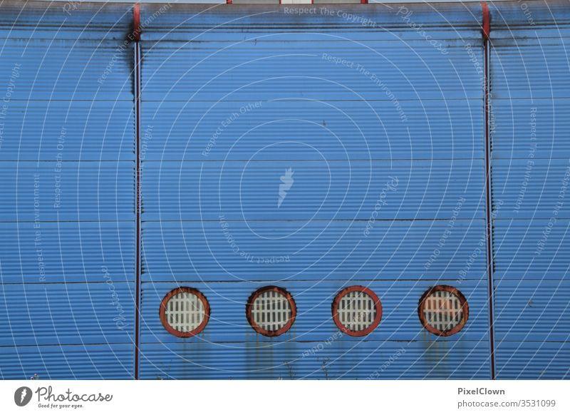 Vier runde Fenster in einer blauen Fassade Wand Mauer Gebäude Architektur Menschenleer Stadt trist Bauwerk