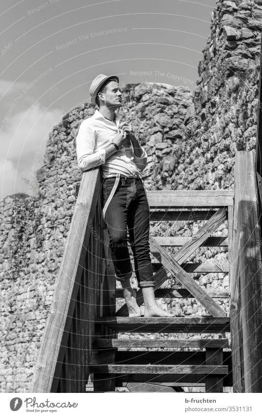 Junger Mann auf einer Holztreppe in einer alten Ruine schauen Schwarzweißfoto ruine hut Mensch Erwachsene Porträt Hemd Barfuß Treppe Holzgeländer zukunft