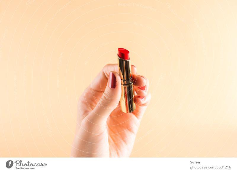 Weibliche Hand hält roten Lippenstift auf hellorangem Glamour Schönheit Frau Mode Farbe schön Make-up Nahaufnahme Accessoire Nägel Personal Mädchen Finger