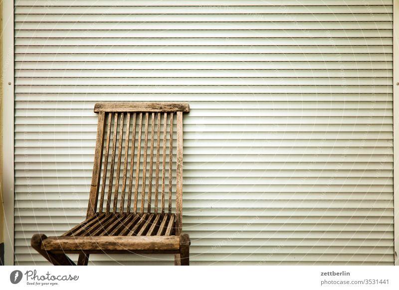 Gartenstuhl vor verschlossener Jalousie jalousie klappstuhl möbel gartenstuhl frei leer erholung ferien kleingarten kleingartenkolonie menschenleer ruhe