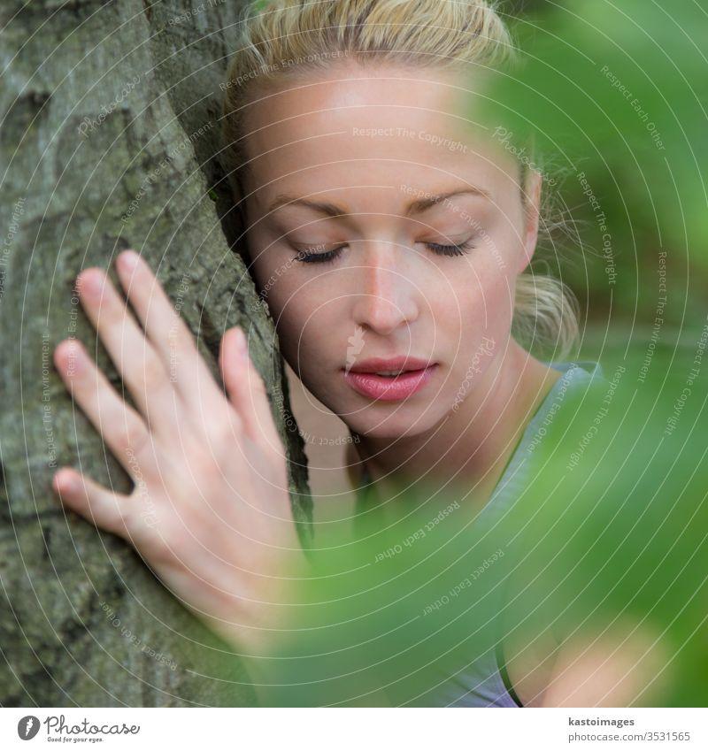 Junge Frau umarmt einen Baum. Umarmung umarmend hugger Umarmen Wald Harmonie Kofferraum Gleichgewicht geistig Spiritualität Arme zuhören Person Holz grün Natur